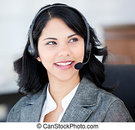 Attractive businesswoman wearing a headset to talk with customers in the office