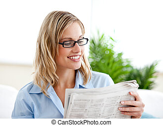 Attractive businesswoman wearing glasses and reading the newspaper sitting on the sofa at home