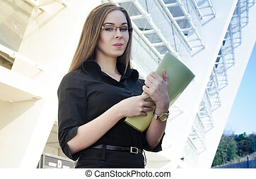Attractive businesswoman wearing glasses holding a folder