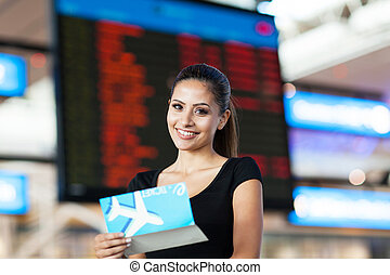 attractive businesswoman with air ticket in front flight information board at airport