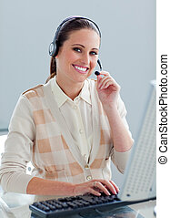 Attractive businesswoman with headset on working at a...
