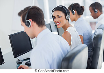 Attractive call centre employee looking over shoulder while...