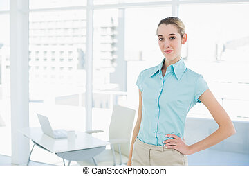 Attractive calm businesswoman posing in her office with hand on hip looking at camera