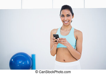 Attractive calm woman text messaging with her smartphone