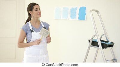Attractive capable woman redecorating her home in a DIY...
