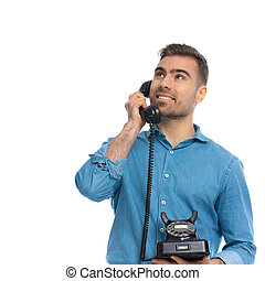 attractive casual man talking on an old telephone and dreaming