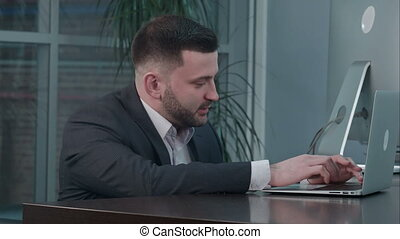 Attractive caucasian businessman using laptop, while talking with partner at workplace