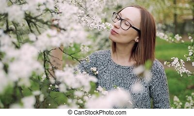 Attractive caucasian girl in glasses enjoys smell of white blossoming cherry. Closeup shot.