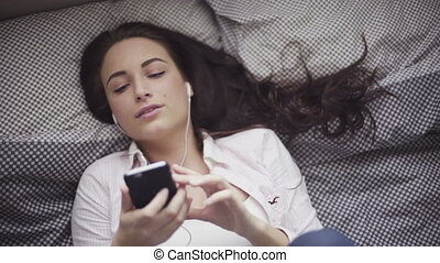Attractive caucasian girl is lying on a bed and listening to the music from her mobile device, earphones plugged-in.