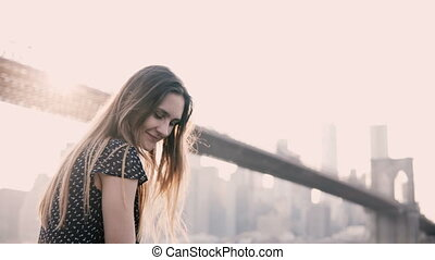 Attractive Caucasian girl looking at camera smiling, sitting on embankment fence New York Brooklyn Bridge sunset view.