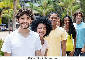 Attractive caucasian hipster man with beard with multi ethnic friends in line