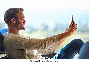 Attractive caucasian man taking a selfie with his mobile phone
