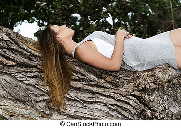 Attractive Caucasian Teen Girl Reclining On Tree Profile