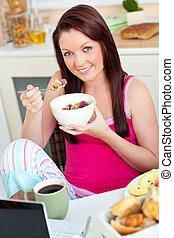 Attractive caucasian woman having breakfast smiling at the camera sitting in the kitchen at home