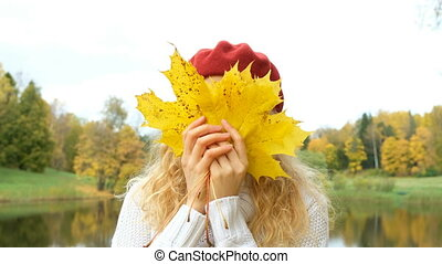 Attractive Caucasian woman posing with maple leaves in autumn Park