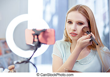Attractive charming woman recording video for her blog