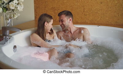 Attractive cheerful couple in hot tub is playing blowing foam, kissing and enjoying romantic moments. Rose petals, flowers and burning candles are visible.
