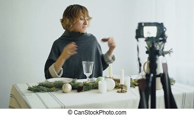 Attractive cheerful woman sitting at the table recording video blog about food decoration design on camera
