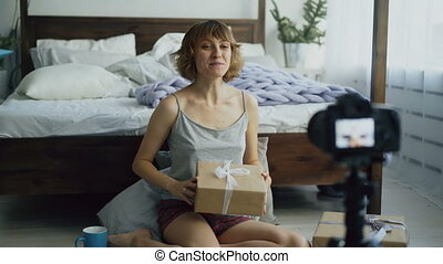 Attractive cheerful woman sitting near bed recording video blog about packing gift box with dslr camera
