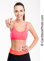 Attractive cheerful young female athlete pointing on you