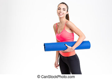 Attractive cheerful young sportswoman holding yoga mat -...