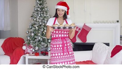 Attractive Christmas cook showing off her cupcakes
