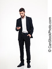 Attractive confident bearded businessman using mobile phone