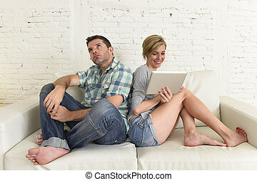 attractive couple at home couch happy woman internet addict on digital tablet ignoring sad husband