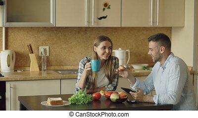Attractive couple chatting and having breakfast in the kitchen