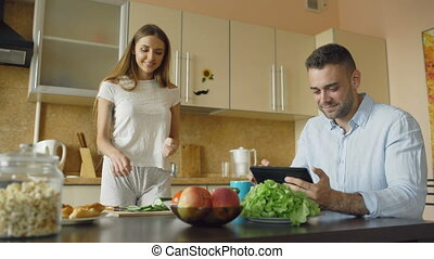 Attractive couple chatting in the kitchen early morning. Beautiful woman feed her husband while cooking breakfast