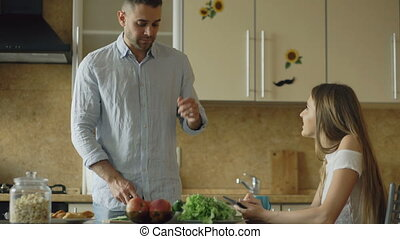 Attractive couple chatting in the kitchen early morning. Handsome man feed his wife while cooking breakfast