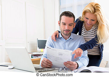 VIew of a Young attractive couple doing administrative paperwork