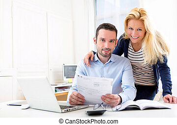 Attractive couple doing administrative paperwork - VIew of a...