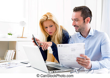 Attractive couple doing administrative paperwork - View of...