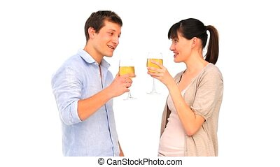 Attractive couple enjoying a glass of white wine against a...