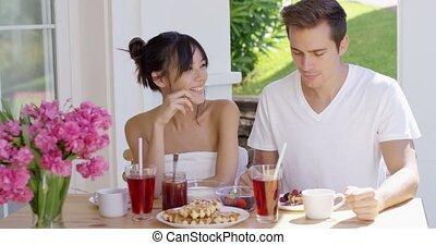 Attractive couple enjoying breakfast outdoors - Attractive...