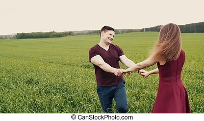 Attractive couple enjoying their time together, walking through a wheat field, holding hands, slow mo, steadicam shot