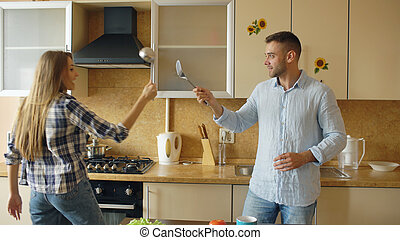 Attractive couple having fun in the kitchen fencing with ladle and spoon while cooking breakfast at home
