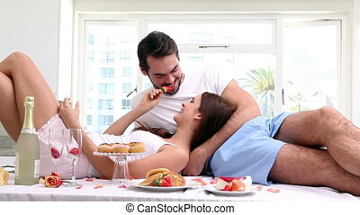 Attractive couple having an indulgent breakfast at home in...