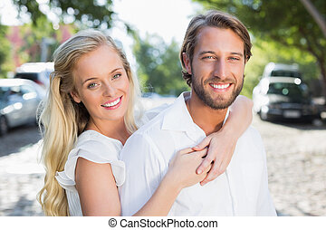 Attractive couple hugging each other and smiling at camera