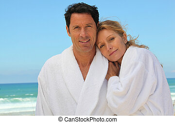 Attractive couple in bathrobes on the beach