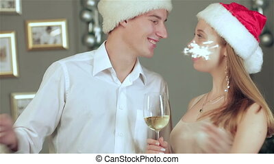 Attractive couple in Santa hat and waving sparklers in a cozy house