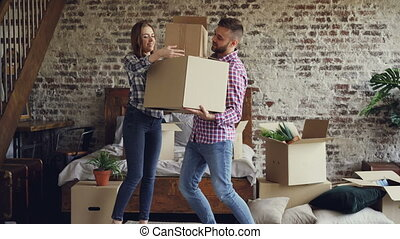 Attractive couple is moving boxes in bedroom in their new home, guy is carrying things while his girlfriend is helping him. People and relocation concept.