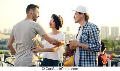 Attractive couple is talking then greeting young man at...