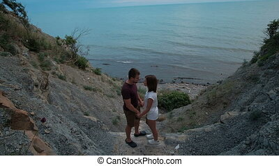 Attractive couple kissing standing on rock by sea shore on summer day outdoors.