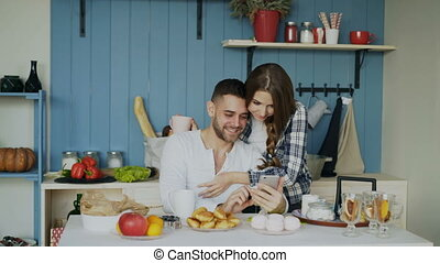 Attractive couple meet in the kitchen at breakfast time and...