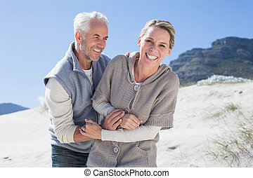 Attractive couple messing about on the beach on a bright but cool day