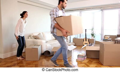 Attractive couple moving boxes into their living room in...