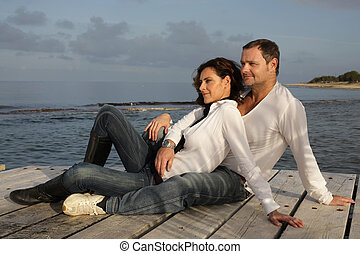 attractive couple on pier - attractive couple relaxing on a...