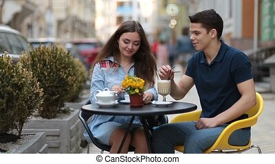 Attractive couple relaxing in sidewalk cafe - Loving couple...
